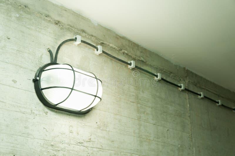 La linterna industrial del vintage con rejilla del metal de la seguridad atada en el muro de cemento del grunge con la bombilla s fotos de archivo libres de regalías