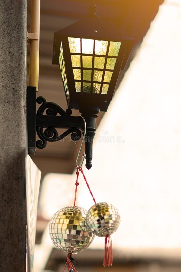 La linterna luminosa amarilla y las bolas reflexivas cuelgan en la fachada del edificio calle, primer, fondo blanco d?a imagen de archivo libre de regalías