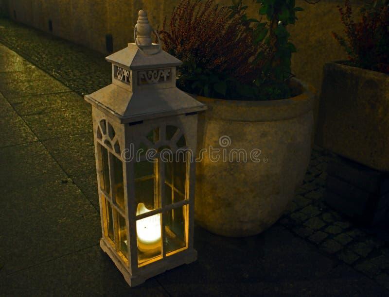 La linterna retra con una vela se coloca en la tierra cerca de un pote beige con las flores imágenes de archivo libres de regalías