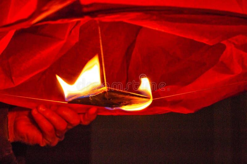 La linterna roja china quema con el fuego en el cielo imagenes de archivo
