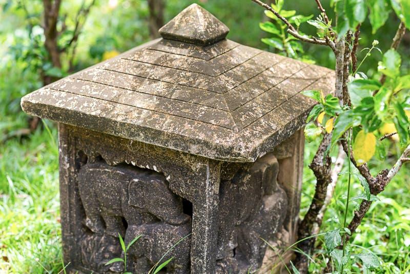 La litera de piedra gris de la calle resistió a viejo con el primer del ornamento en el fondo del jardín imagenes de archivo