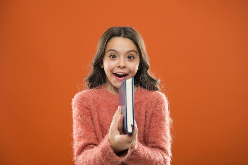 La littérature d'enfants Le livre de prise de fille a lu l'histoire au-dessus du fond orange L'enfant apprécient le livre de lect photo libre de droits
