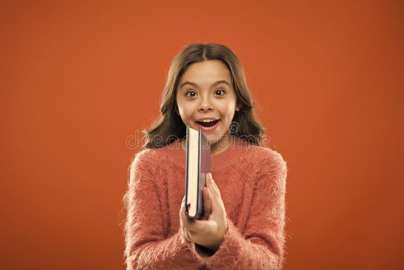 La litt?rature d'enfants Le livre de prise de fille a lu l'histoire au-dessus du fond orange L'enfant appr?cient le livre de lect image libre de droits