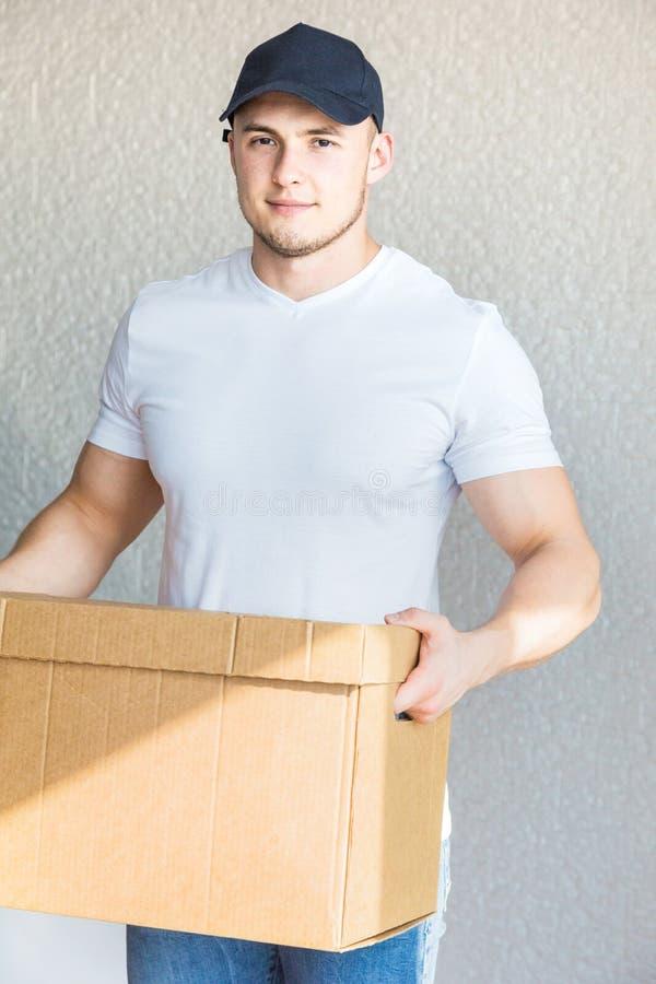 La livraison forte, bo?tes en carton musculaires de chargement d'homme pour se d?placer ? un appartement travailleur professionne photos libres de droits
