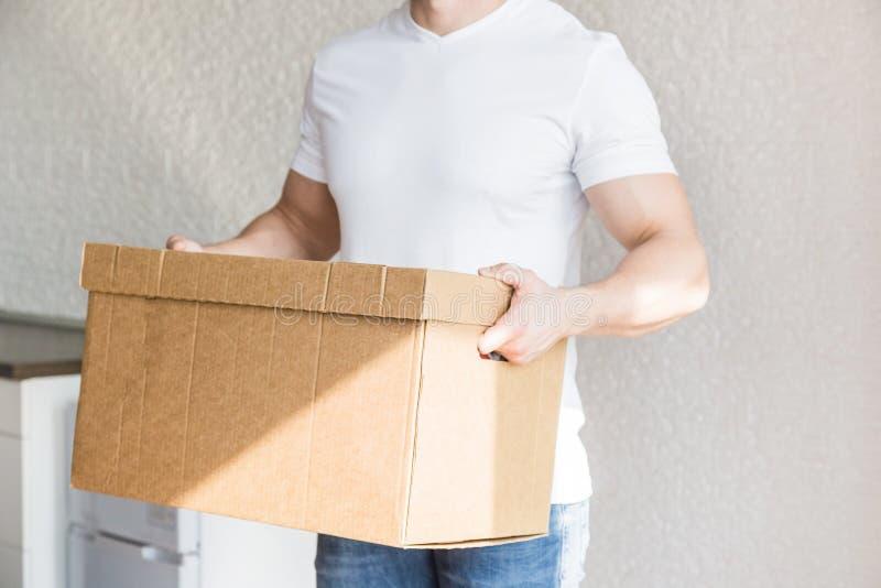 La livraison forte, bo?tes en carton musculaires de chargement d'homme pour se d?placer ? un appartement travailleur professionne image libre de droits