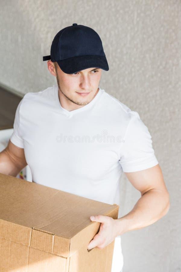 La livraison forte, bo?tes en carton musculaires de chargement d'homme pour se d?placer ? un appartement travailleur professionne photographie stock libre de droits