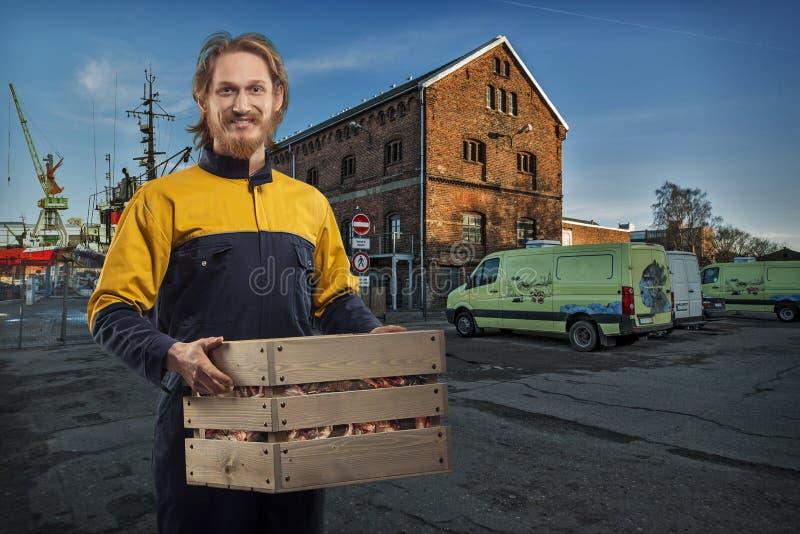 La livraison ou homme de moteur avec la boîte dans le port photos stock