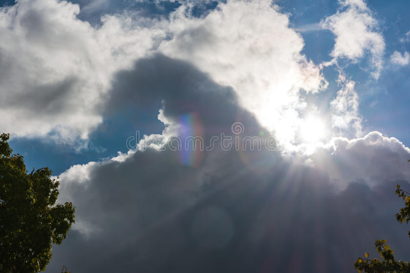La llamarada de Sun que viene de detrás rayos de las nubes pone en contraste el cielo azul marino imagen de archivo libre de regalías