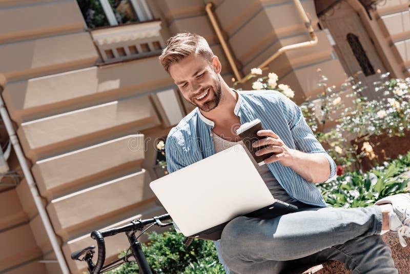 La llave al éxito es acción Hombre sonriente joven que se sienta en el parque, sosteniendo su ordenador portátil y una taza de ca fotografía de archivo