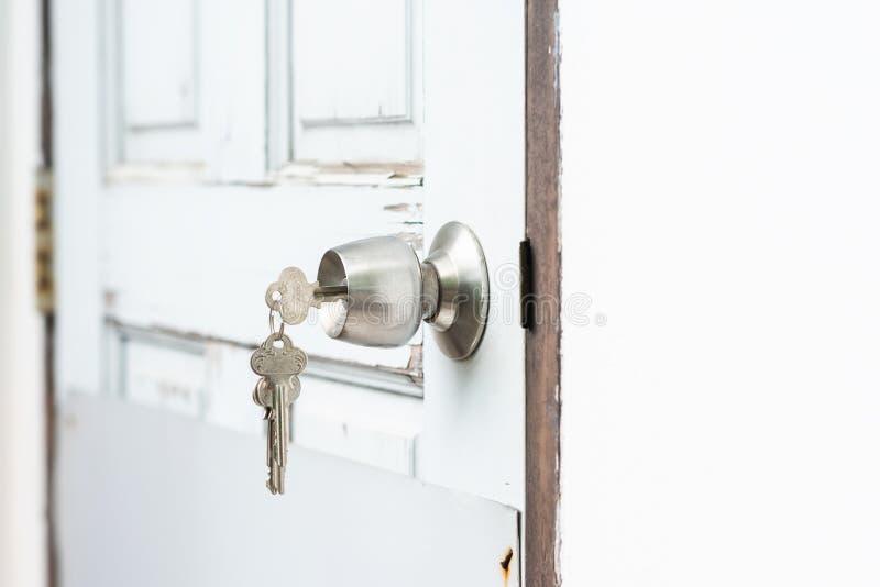 La llave de parte movible en cerradura del agujero o desbloquea la puerta imagen de archivo