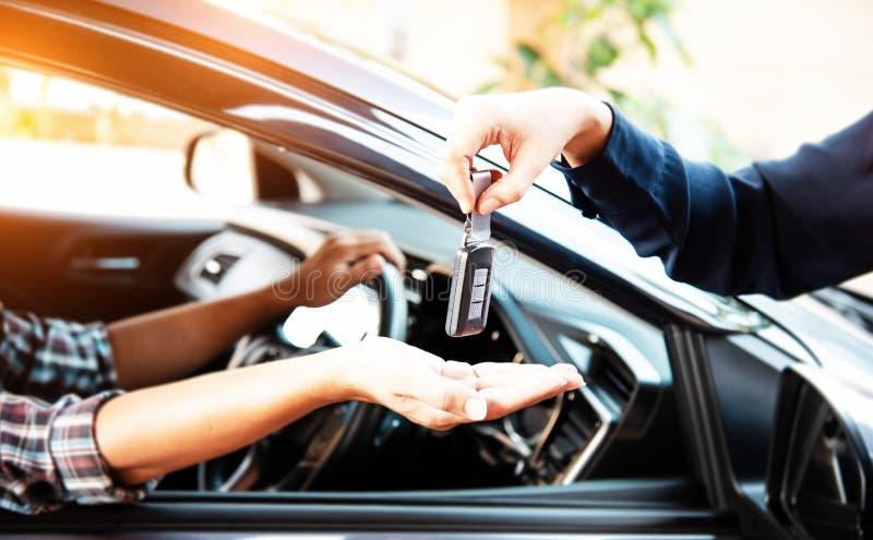 La llave del auto remoto estaba mandando de la mano de la señora a la mano del conductor, tono de luz cálido imágenes de archivo libres de regalías