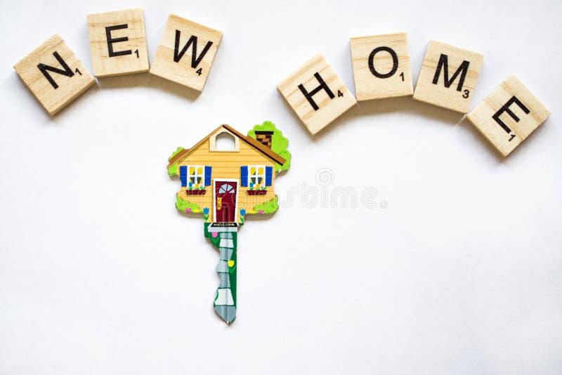 La llave está bajo la forma de casa en un fondo blanco y bloques de madera con la palabra nuestro hogar foto de archivo libre de regalías