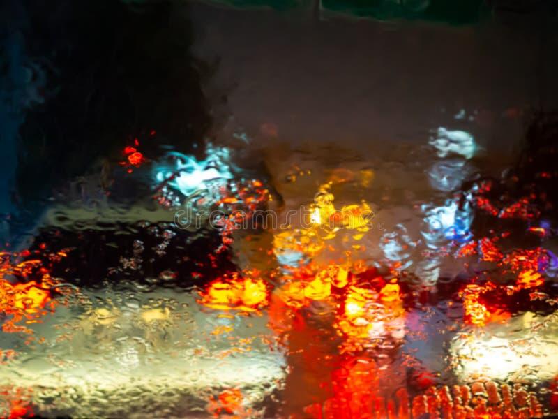 La lluvia borrosa cae en la ventanilla del coche con el bokeh de la luz del camino en fondo del extracto de la estación de lluvia fotos de archivo