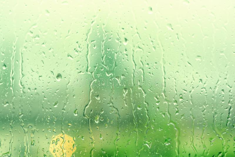 La lluvia cae en ventana con el árbol verde como fondo Gotas naturales del agua sobre el vidrio Foco selectivo foto de archivo
