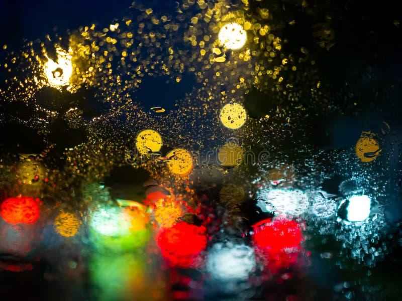 La lluvia cae en la ventanilla del coche con el bokeh de la luz del camino en fondo del extracto de la estación de lluvias fotos de archivo libres de regalías