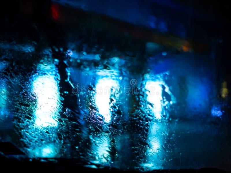 La lluvia cae en la ventanilla del coche con el bokeh de la luz del camino en fondo del extracto de la estación de lluvias imágenes de archivo libres de regalías