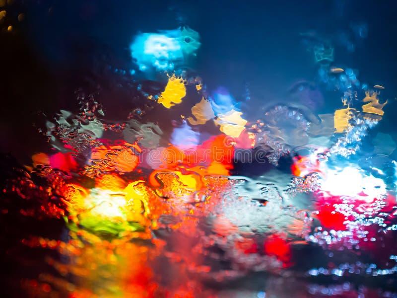 La lluvia cae en la ventanilla del coche con el bokeh de la luz del camino en fondo del extracto de la estación de lluvias fotos de archivo
