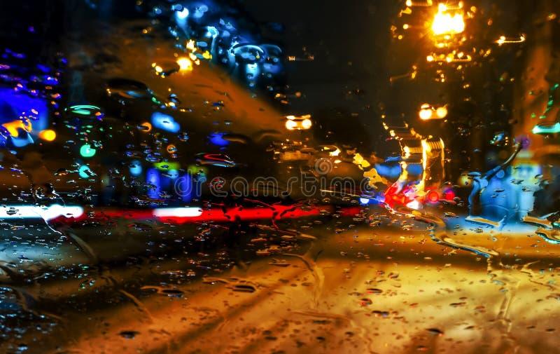 La lluvia cae en la ventanilla del coche con el bokeh de la luz del camino, vida de ciudad en noche en el fondo del extracto de l imágenes de archivo libres de regalías