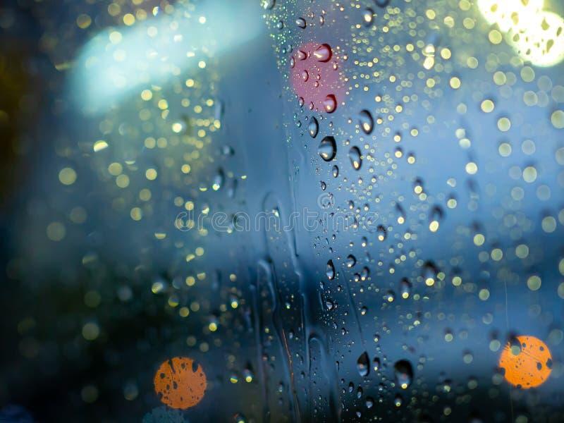 La lluvia cae textura en la ventanilla del coche con el fondo abstracto del bokeh colorido fotografía de archivo libre de regalías