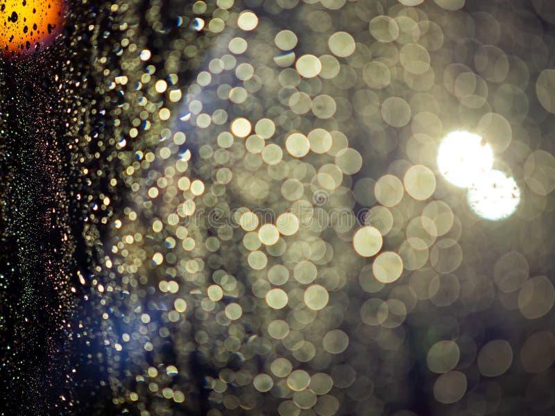 La lluvia cae textura en la ventanilla del coche con el fondo abstracto del bokeh colorido fotos de archivo