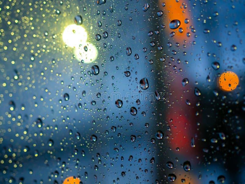 La lluvia cae textura en la ventanilla del coche con el fondo abstracto del bokeh colorido imagen de archivo libre de regalías