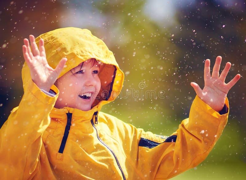 La lluvia de cogida del niño feliz cae en jardín de la primavera foto de archivo