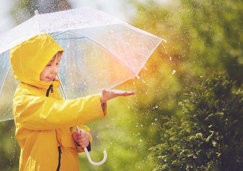 La lluvia de cogida del niño feliz cae en parque de la primavera imagen de archivo