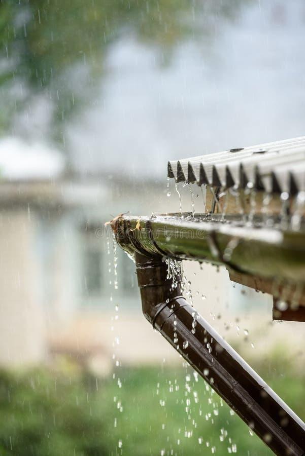 La lluvia fluye abajo de un tejado abajo imágenes de archivo libres de regalías