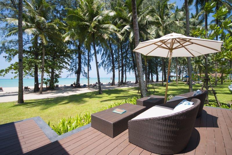 La località di soggiorno dell'hotel con l'ombrello e la sedia trascurano il mare immagine stock