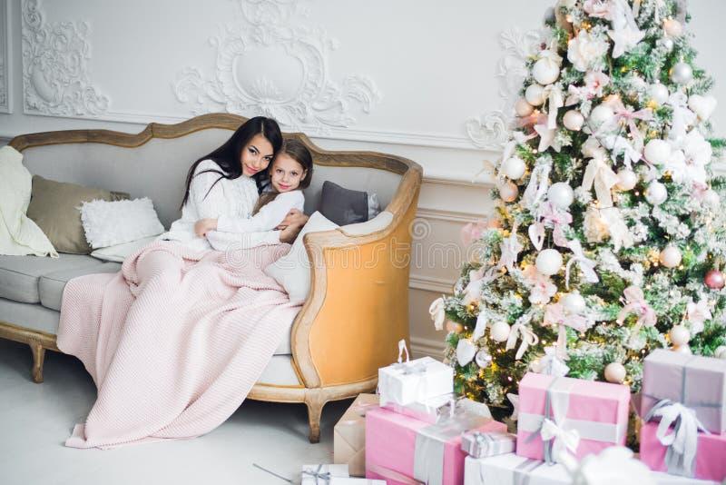 La localización de dos muchachas felices, de la madre y de la hija en un sofá en la Navidad adornó el sitio imagen de archivo