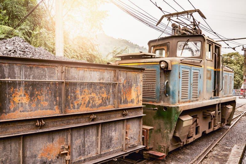 La locomotiva a scartamento ridotto elettrica sta con il treno merci immagini stock libere da diritti