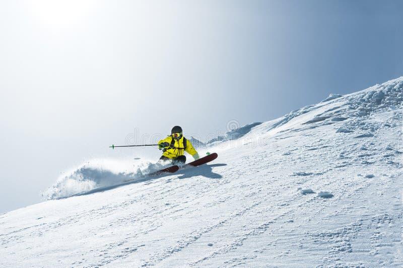 La longitud total del esquí en polvo fresco de la nieve Esquiador profesional fuera de la pista en un día soleado foto de archivo
