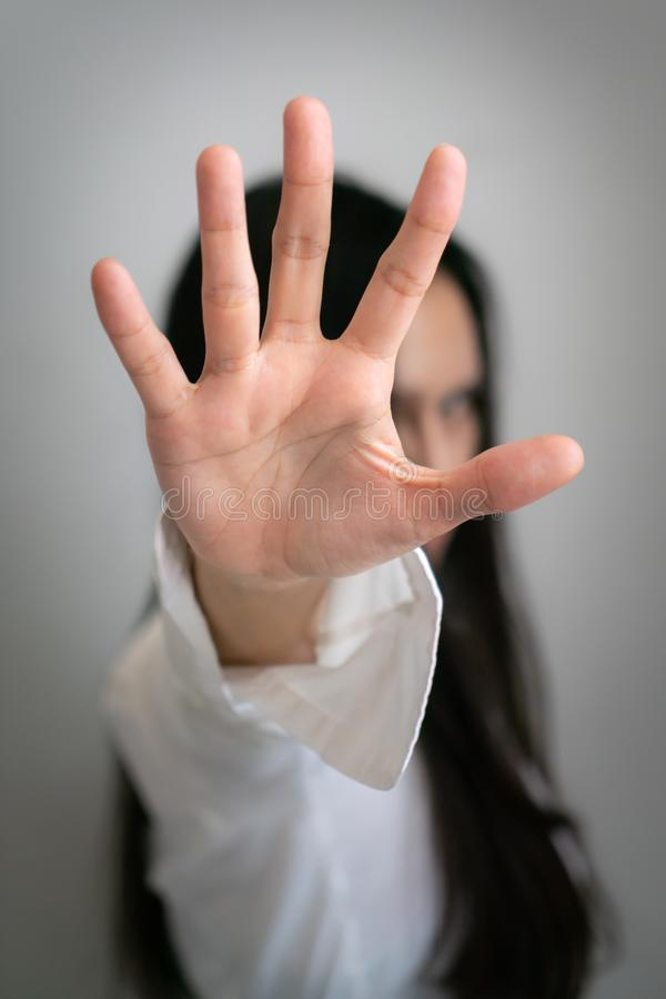 La longue femme asiatique de cheveux noirs se lève sa main jusqu'à arrêter quelque chose photo libre de droits