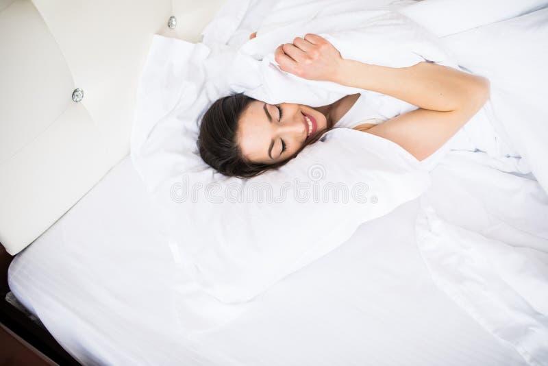 La longue femme de cheveux de belle brune se trouve sur le linge de lit blanc dans la lumière molle de matin Concept de la vie he photo stock