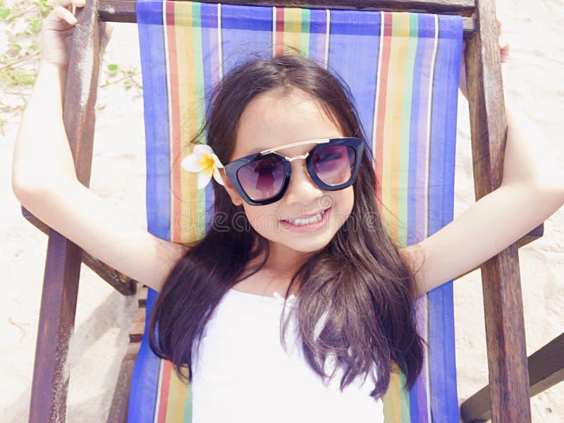 La longue fille asiatique de cheveux noirs porte les lunettes de soleil noires et le blanc image stock
