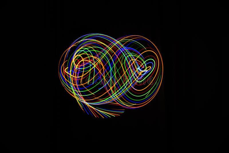 La longue photographie d'exposition a fait avec la peinture légère de diverses couleurs sur un fond noir, des vagues, des courbes images stock