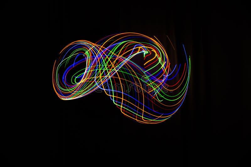 La longue photographie d'exposition a fait avec la peinture légère de diverses couleurs sur un fond noir, des vagues, des courbes photographie stock libre de droits