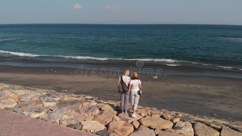 la longueur aérienne de vol du bourdon 4K de jeunes couples sur le sable noir sauvage échouent Île de Bali photographie stock libre de droits