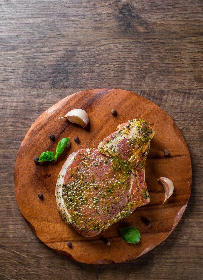 La lonza di maiale cruda taglia la bistecca a pezzi marinata della carne per il bbq sulla tavola di legno fotografia stock