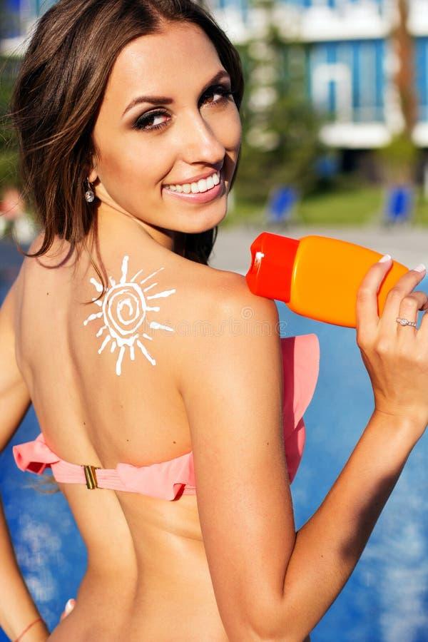 La lotion de protection solaire sur des filles épaulent près de la piscine photos stock
