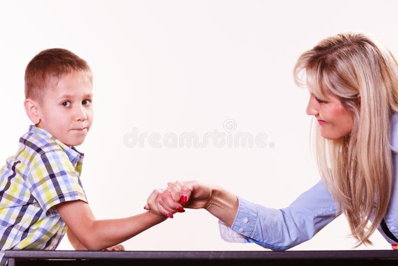 La lotta del braccio del figlio e della madre si siede alla tavola fotografie stock libere da diritti
