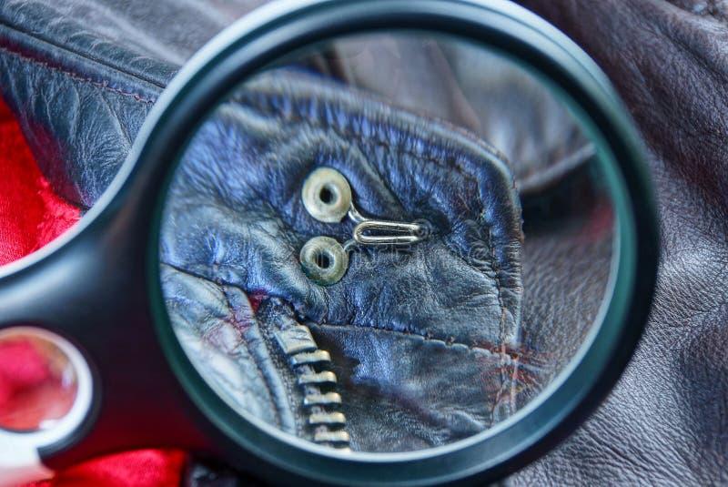 La loupe noire magnifie les rivets et la fermeture éclair en métal sur le cuir brun photos libres de droits