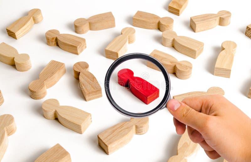 La loupe regarde la figure humaine rouge parmi beaucoup d'autres personnes Concept, recrutement et personnel de recherche des emp photo libre de droits