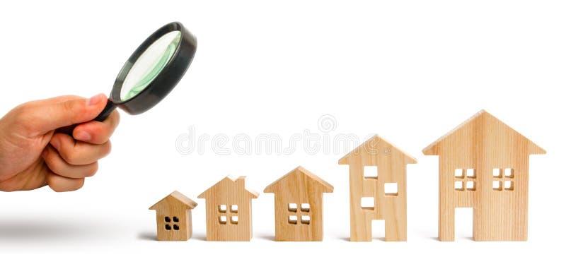 La loupe regarde les maisons en bois se tiennent dans l'ordre montant sur un fond blanc Isolez le concept de l'augmentation images stock