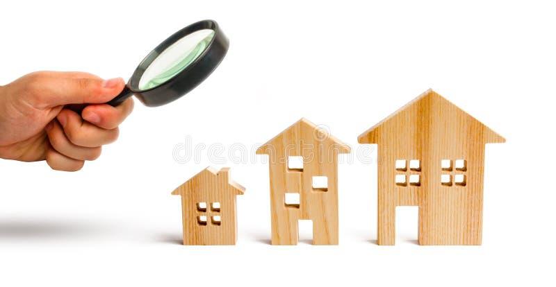 La loupe regarde les maisons en bois se tiennent dans l'ordre montant sur un fond blanc Isolez le concept de l'augmentation photos libres de droits