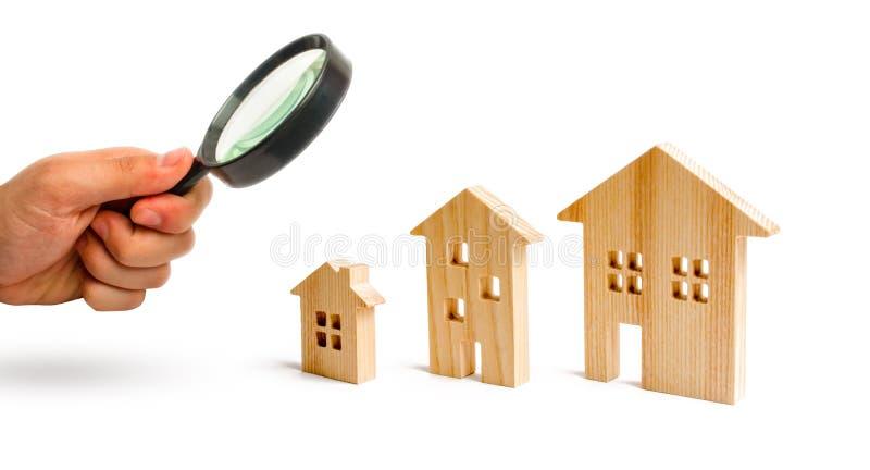 La loupe regarde les maisons en bois se tiennent dans l'ordre montant sur un fond blanc Isolez le concept de l'augmentation photos stock