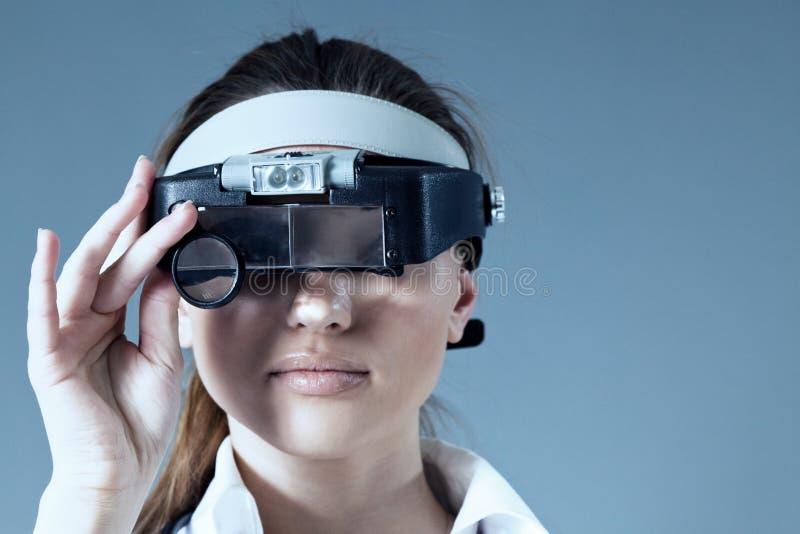 La loupe s'usante de jeune docteur féminin équipent image stock