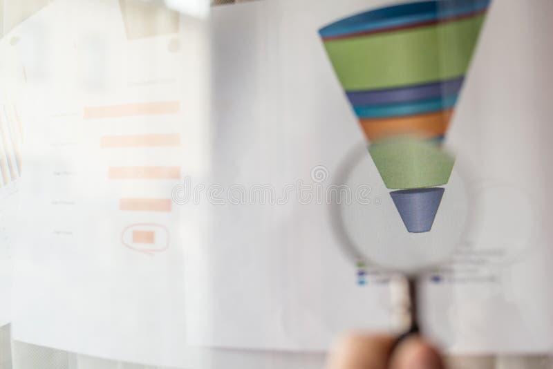 La loupe sur un diagramme coloré d'entonnoir a imprimé sur une feuille de papier blanche au cours d'une réunion d'affaires photos libres de droits