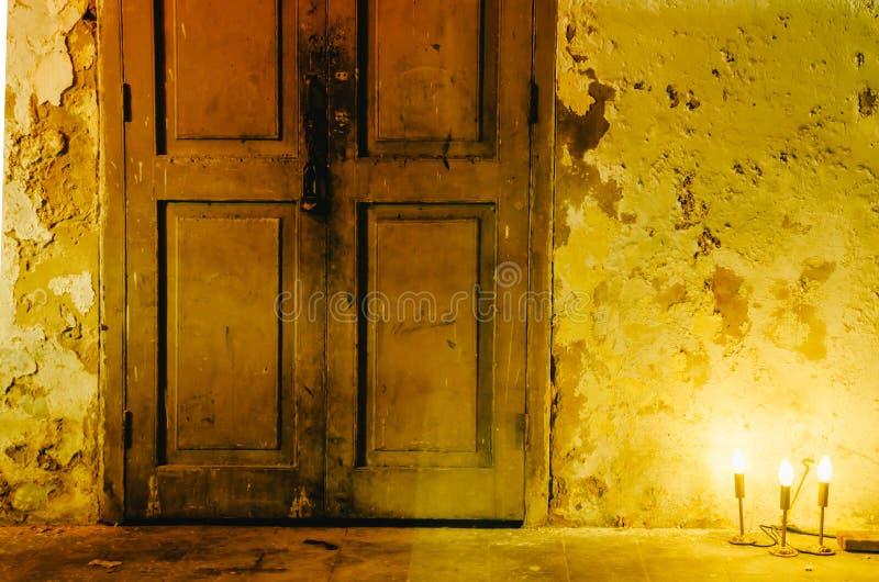 La luce arancio dalla lampada nera era anteriore sulla vecchia parete sporca bianca che ha macchia nera allo spazio della copia e immagini stock