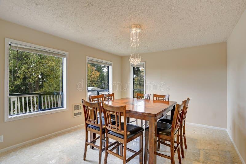 La luce beige ha riempito la sala da pranzo di insieme di legno del tavolo da pranzo immagine stock libera da diritti